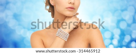 beauty, luxury, people, holidays and jewelry concept - close up of beautiful woman with pearl earrings and bracelet over blue lights background - stock photo