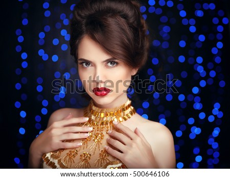 Beauty Makeup. Beautiful elegant woman in fashion golden dress. Hairstyle. Vogue style.  Gorgeous girl model isolated on blue party lights background.