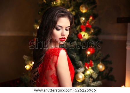 Beauty makeup. Elegant brunette woman portrait  in red dress over christmas tree lights background. Happy new year. Winter holiday home party.
