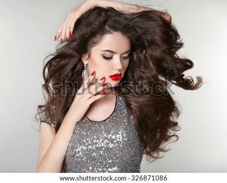 Beauty Makeup. Healthy Long Hair. Beautiful brunette girl with brown curly hair, wavy hairstyle. Manicured nails. Fashion attractive young woman.  - stock photo
