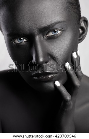 Beauty makeup portrait of young beautiful fashion model with black skin colored face and blue eyes. studio shot. looking at camera and touch her face with fingers. - stock photo