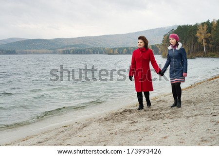 beauty mature woman in red topcoat with young daughter, walking outdoor on water moorage for boat, in autumn cold overcast day