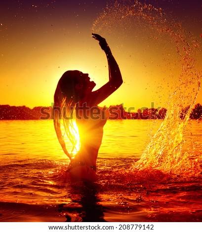 Beauty Model Girl Splashing Water. Teen girl Swimming and splashing on summer beach over sunset. Beautiful Woman Enjoying nature - stock photo