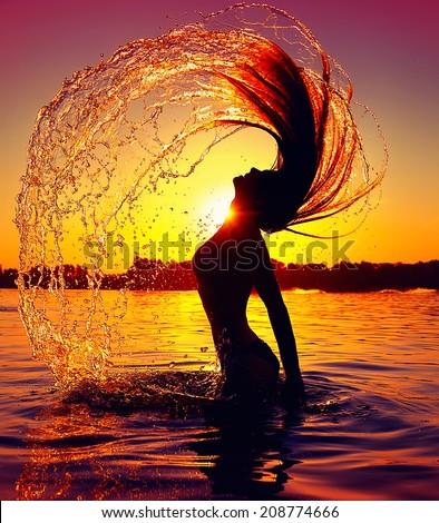 Beauty Model Girl Splashing Water with her Hair. Teen girl Swimming and splashing on summer beach over sunset. Beautiful Woman in Water  - stock photo