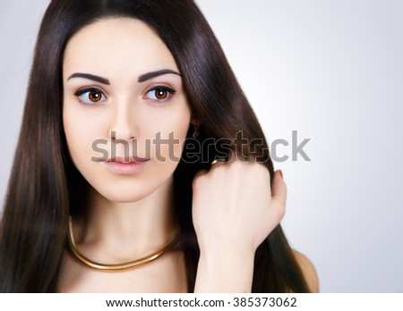 Beauty Model girl with Healthy Brown Hair. Beautiful brunette woman touching her long smooth shiny straight hair. Hairstyle. Hair cosmetics, haircare. - stock photo