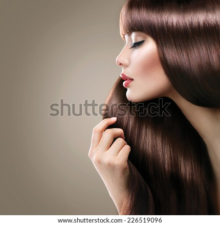 Beauty Model girl with Healthy Brown Hair. Beautiful woman touching her long smooth shiny straight hair. Hairstyle. Hair cosmetics, haircare - stock photo