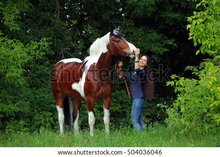 Beauty model hugging a horse in nature background