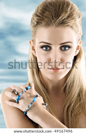 Beauty model portrait on blue sky background - stock photo