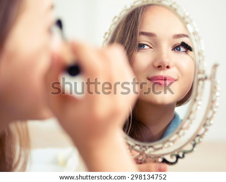 Beauty model teenage girl looking in the mirror and applying mascara make up. Beautiful young woman apply makeup - stock photo