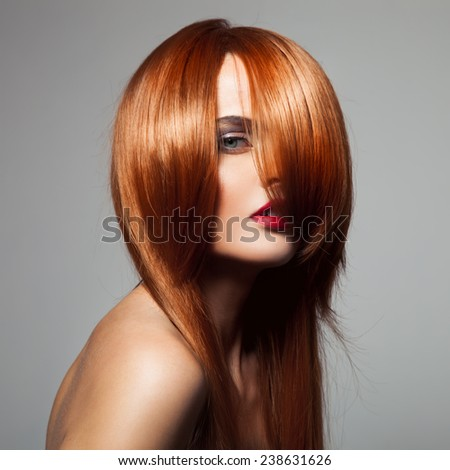Beauty model with perfect long glossy red hair. Close-up portrait. - stock photo