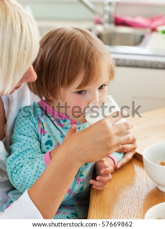 Beauty mother and daughter having breakfast in the kitchen - stock photo