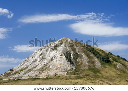 Beauty mountain on a field. Shikhan, Ural Mountain. Blue sky and white clouds - stock photo
