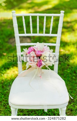 Beauty of colored flowers. Bridal accessories. Close-up bunch of florets. Details for marriage and for married couple. Wedding bouquet with peonies, roses and orchids on the white chair - stock photo