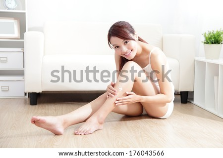 Beauty of young pretty woman with perfect shape and applying cream on her attractive legs indoors at home, asian beauty - stock photo