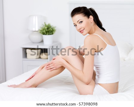 Beauty of young pretty woman with perfect shape and clean fresh beatiful legs - indoors - stock photo