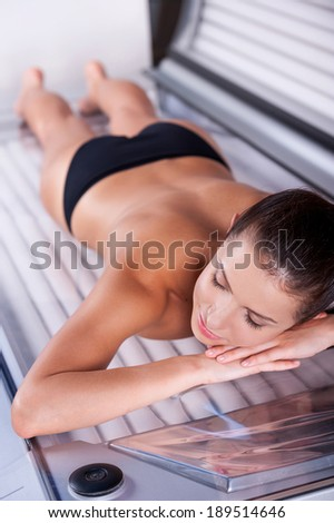 Beauty on tanning bed. Top view of beautiful young shirtless woman lying on tanning bed and keeping eyes closed - stock photo