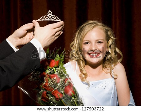 Beauty pageant winner smiling, holding roses and getting her crown - stock photo