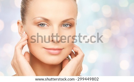 beauty, people and body care concept - beautiful young woman touching her face over blue holidays lights background - stock photo