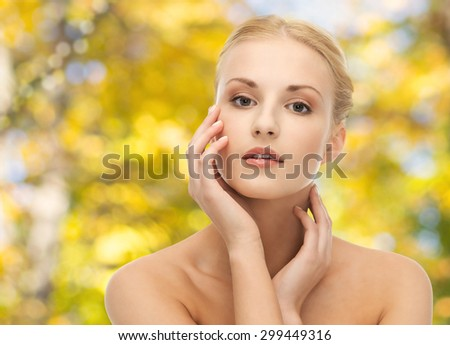 beauty, people and body care concept - beautiful young woman touching her face over yellow autumn background - stock photo