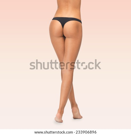 beauty, people and bodycare concept - close up of female legs in black bikini panties over pink background