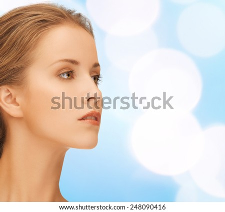 beauty, people and health concept - beautiful young woman face over blue lights background - stock photo