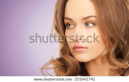 beauty, people and health concept - beautiful young woman face over violet background - stock photo