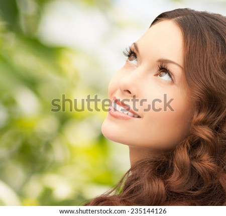 beauty, people and health concept - beautiful young woman looking up over green background