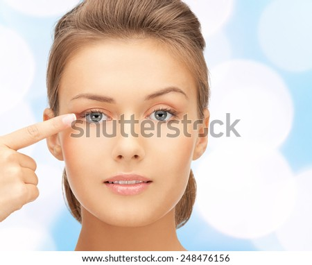 beauty, people and health concept - beautiful young woman pointing finger to her eye over blue lights background - stock photo