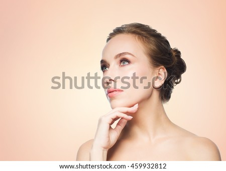 beauty, people and health concept - beautiful young woman touching her face over beige background - stock photo