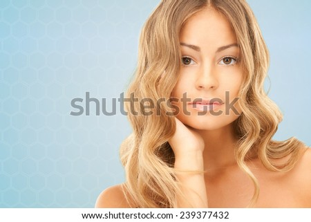 beauty, people and health concept - beautiful young woman with bare shoulders over blue background - stock photo