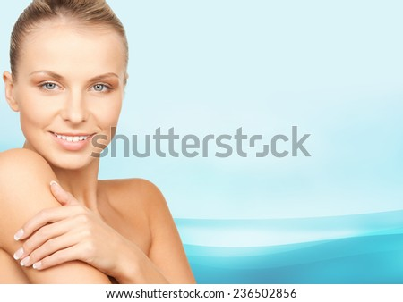 beauty, people and health concept - beautiful young woman with bare shoulders over blue waves background