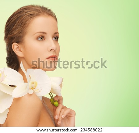 beauty, people and health concept - beautiful young woman with orchid flowers and bare shoulders over green background - stock photo