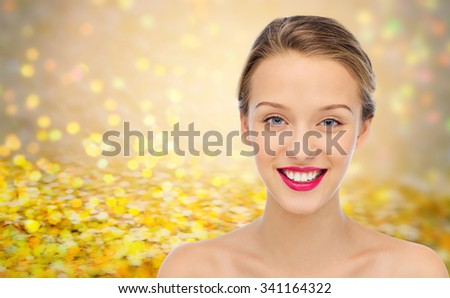 beauty, people and health concept - smiling young woman face with pink lipstick on lips and shoulders over golden glitter or holidays lights background - stock photo