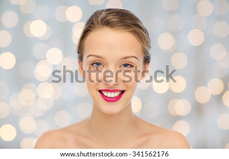 beauty, people and health concept - smiling young woman face with pink lipstick on lips and shoulders over holidays lights background - stock photo