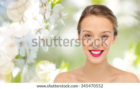 beauty, people and health concept - smiling young woman face with pink lipstick on lips and shoulders over summer green natural background with cherry blossom - stock photo
