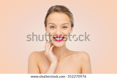 beauty, people and health concept - smiling young woman face with pink lipstick on lips and shoulders over beige background - stock photo