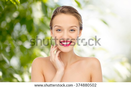 beauty, people and health concept - smiling young woman face with pink lipstick on lips and shoulders over green natural background - stock photo