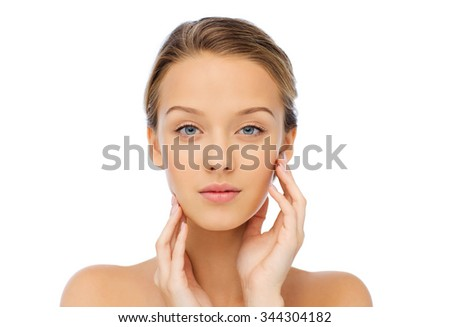 beauty, people and health concept - young woman with bare shoulders touching her face - stock photo