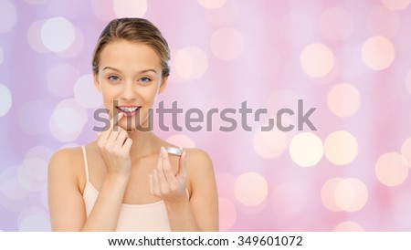 beauty, people and lip care concept - smiling young woman applying lip balm to her lips over pink lights background - stock photo