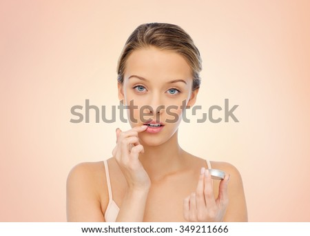 beauty, people and lip care concept - young woman applying lip balm to her lips over beige background - stock photo