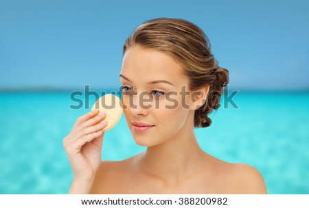 beauty, people and skincare concept - young woman cleaning face with exfoliating sponge over blue sea and sky background - stock photo