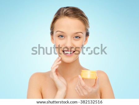 beauty, people, cosmetics, skincare and cosmetics concept - happy young woman applying cream to her face over blue background - stock photo