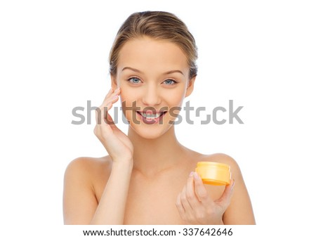 beauty, people, cosmetics, skincare and cosmetics concept - happy young woman appying cream to her face - stock photo