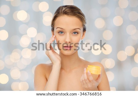 beauty, people, cosmetics, skincare and cosmetics concept - young woman applying cream to her face over holidays lights background - stock photo