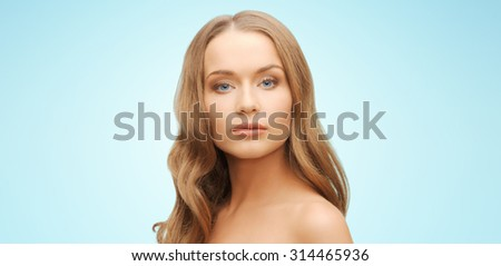beauty, people, hair care and health concept - beautiful young woman face over blue background - stock photo