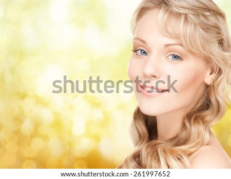 beauty, people, hair care and health concept - beautiful young woman face with long wavy hair over yellow lights background