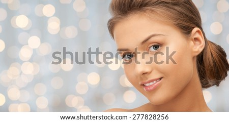 beauty, people, holidays, luxury and health concept - beautiful young woman face over lights background - stock photo