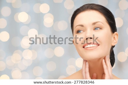 beauty, people, holidays, luxury and health concept - beautiful young woman touching her face and neck over lights background - stock photo