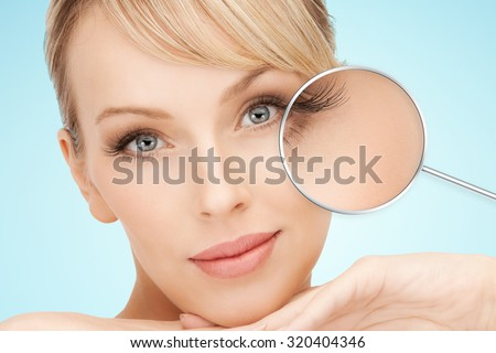 beauty, people, lash extension and makeover concept - beautiful young woman face over blue background with lashes in magnifying glass - stock photo