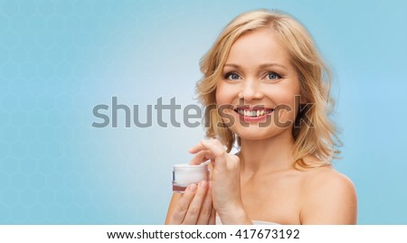 beauty, people, skincare and cosmetics concept - happy woman with cream jar over blue background